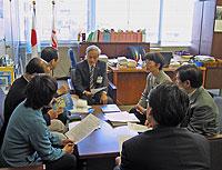 田村教育長(正面)と懇談する議員団。教育長の後ろには日の丸が掲揚されています