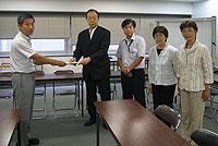 藤田格基地対策担当理事(左)に申し入れ書を手渡す(左から)大貫憲夫、かわじ民夫、関美恵子、白井まさ子の各市議