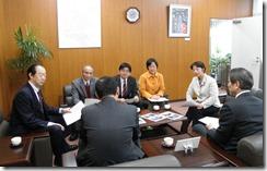 写真を示しながら説明する日本共産党市議団(向こう側)、と説明を受ける柏崎副市長等(手前背中)