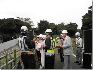 現場を見下ろせる丘の上で、説明を受ける議員団。